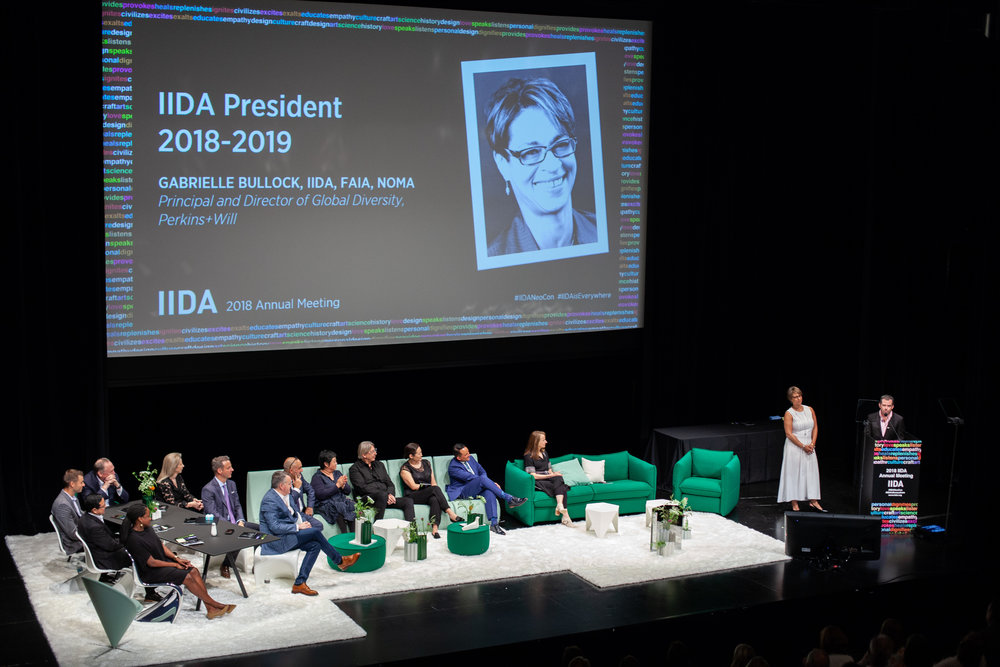 [Image description: A panel of people are on a stage all looking toward a podium where Gabrielle Bullock is about to speak as the incoming president of the International Interior Design Association's international board of directors. There is an image of Gabrielle projected onto a big screen above the stage.]