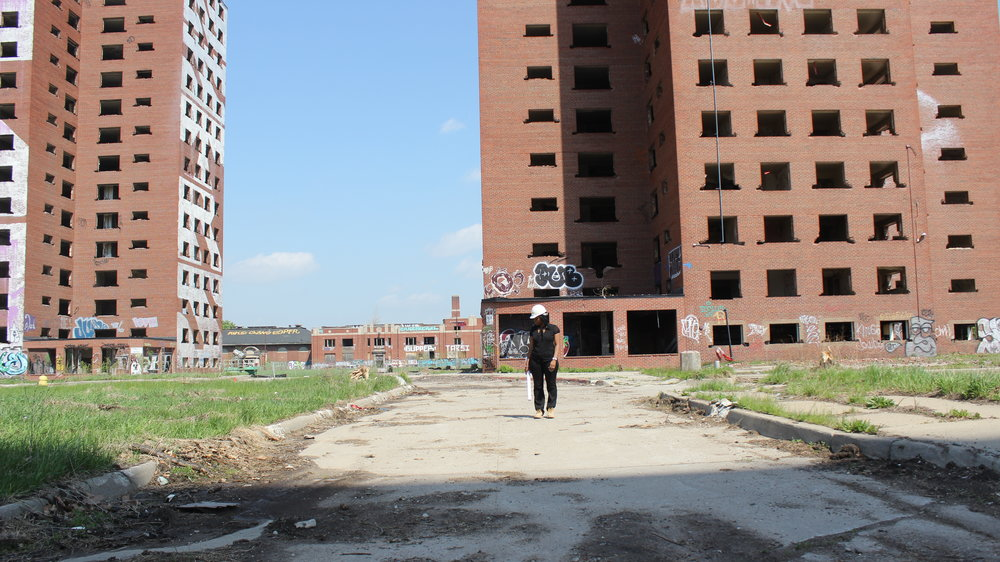 [Image description: Tiffany Brown stands at a work site. She is wearing a white hard hat and holding architectural plans. Behind her are dilapidated brick buildings.]