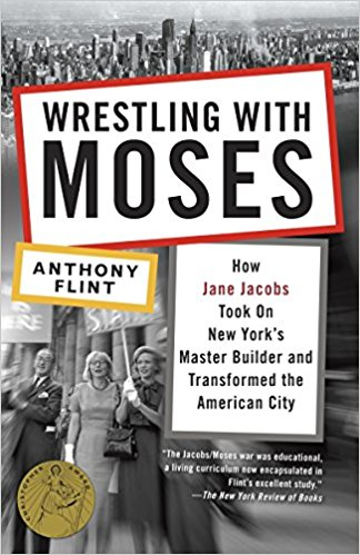 Image description: Cover image for Wrestling with Moses:How Jane Jacobs Took On New York's Master Builder and Transformed the American City. The background photo shows a group of men and women (circa 1950s) holding protest signs. At the top of the cover, there is an overhead shot of the New York City skyline.