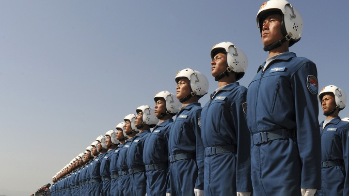 Image description: A photo of military pilots in blue uniforms and white helmets all standing at attention.