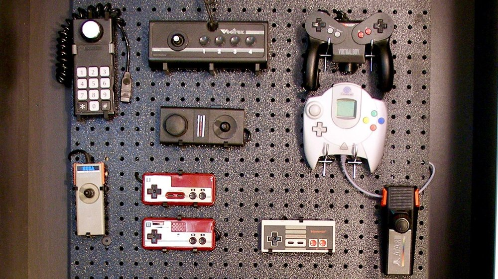 "Image description: A cropped view of John Porter's ""Wall of Exclusion"" which is a pegboard that displays an assortment of video game controllers that require the use of hands. Photo courtesy of John Porter."