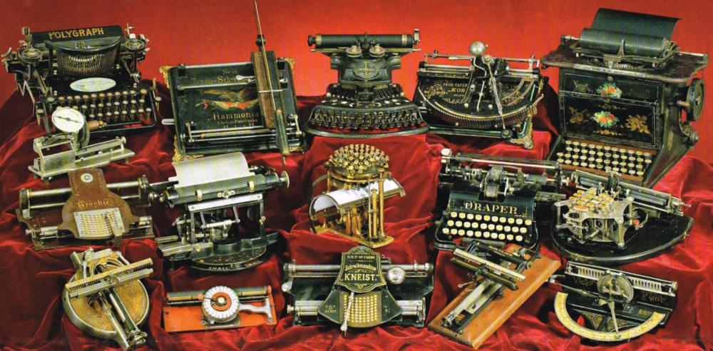 [Image description: Assorted vintage typewriters arranged for display on a red velvet cloth. Image source: ozTypewriter.]