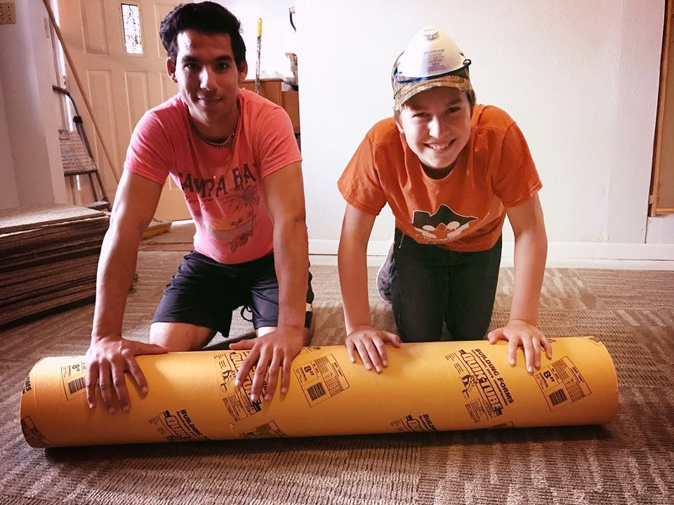 Nathan rolling out carpet.jpg