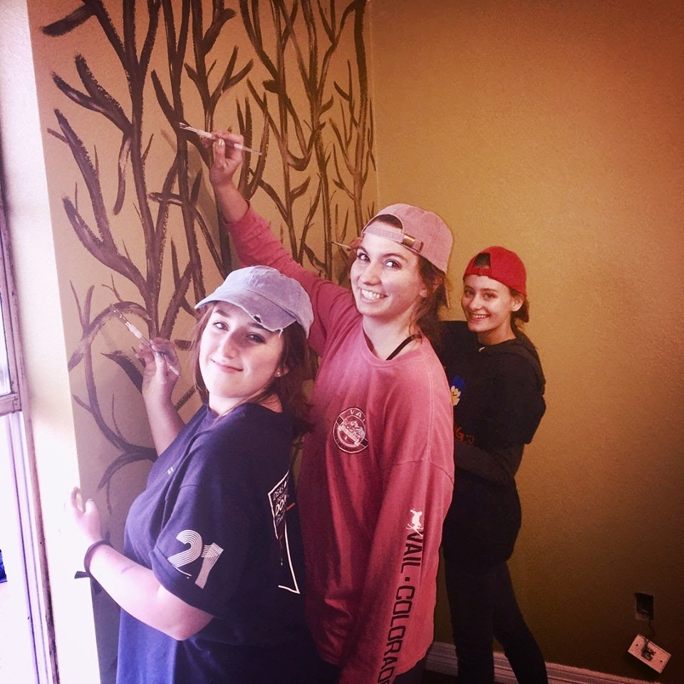 Girls painting trees on wall Haiker Home.jpg