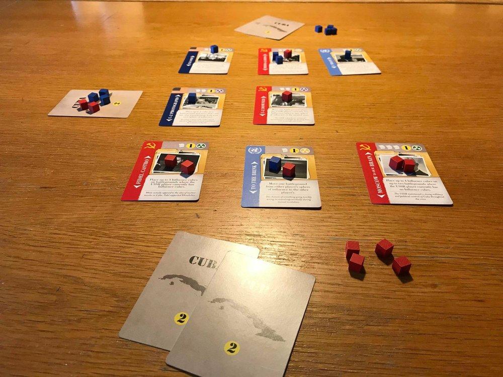 Et eksempel på hvordan et spil kan se ud. Hver spiller har 3 kort i deres egen zone, og der er 3 kort i den neutrale zone .