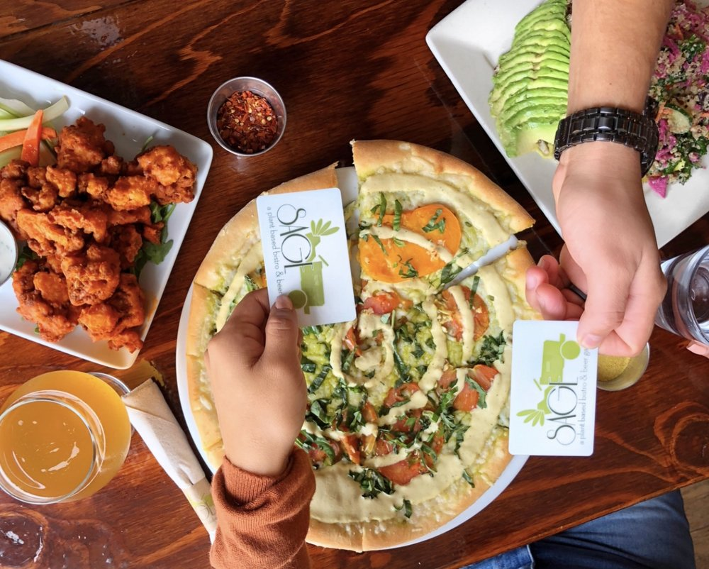 Exchanging Sage gift cards over a meal.