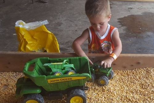 preschool farm activities to do at home, corn in a bin, sensory play, playing with john deere tractors at obloy family ranch in merritt island florida