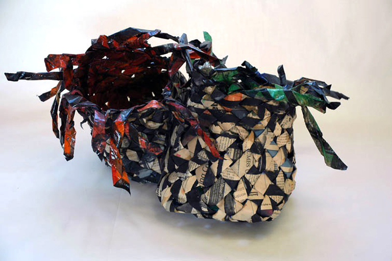 """Two Sides of a Story:  My three boys, like any siblings close in age, would argue often and turn to me to arbitrate and decide whose perspective was right. These baskets, woven in newspaper full of opinions and its angles of stories reminded me of my boys arguments that they aptly spun in their favor.  8""""h x 15""""w x 8""""d  newspaper, lacquer  2007"""