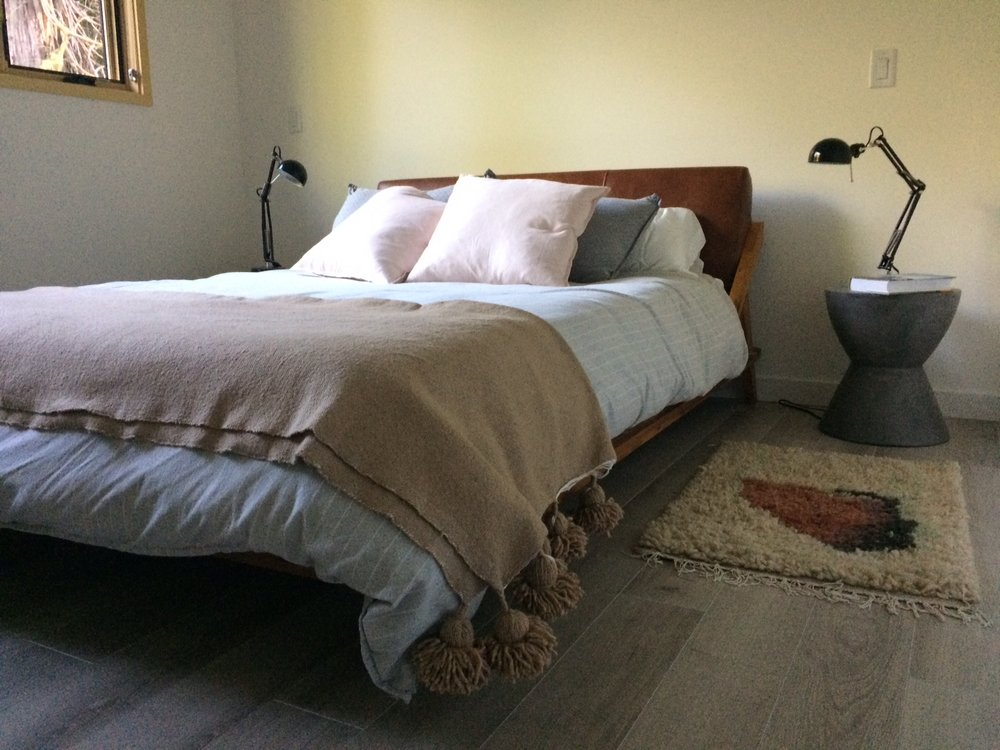 A leather headboard bed by  CB2  welcomes guests to relax. Area rug is hand crafted in Mexico purchased from local Tofino retailer  Merge , and a hand made tassel blanket from Morocco from  Artizanry  acts as the coverlet. Side tables are cast in concrete from  Sun Pan .