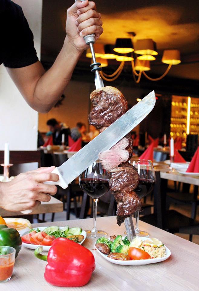 """Brasil Brasileiro! - Speisen wie die Gauchos - Köstliche brasilianische Grillspezialitäten von unsrem besonderen Rodizio-Grill.Unser Rindfleisch wird ausschließlich aus Brasilien und Argentinien importiert und nach traditionellen brasilianischen Hausrezeptureneingelegt, gewürzt und abgeschmeckt.Direkt vom Grill gehen unsere Grillmeister, die Cortadores, mit den herrlich anzuschauenden Spießen, mit über 10 Rodizio-Fleisch- Spezialitäten, von Tisch zu Tisch und schneiden ihnen das köstliche Fleisch direkt auf Ihren Teller, bis Sie """"Halt"""" rufen.Das erstklassige All-You-Can-Eat-Buffet rundet das Rodizio Geschmackserlebnis ab."""