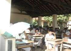 Children taking exams sheltering under an umbrella at the Unawatuna Maha Vidyalaya