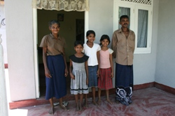 Sumanawathie and her family standing proudly on the porch of their new house