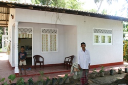 Premasiri and one of his three sons outside their new house
