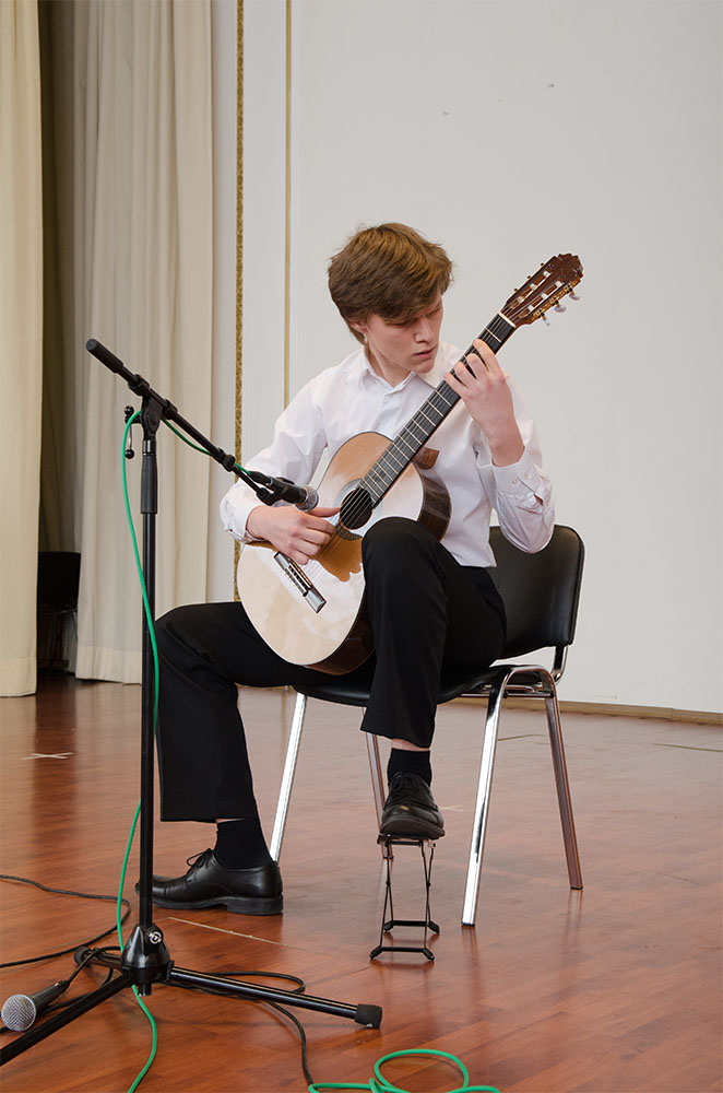 "(15–18) Nikita Krylov, on a classical guitar played ""Pilot"" by Alfred Schnittke. It is the performance of a serious musician."