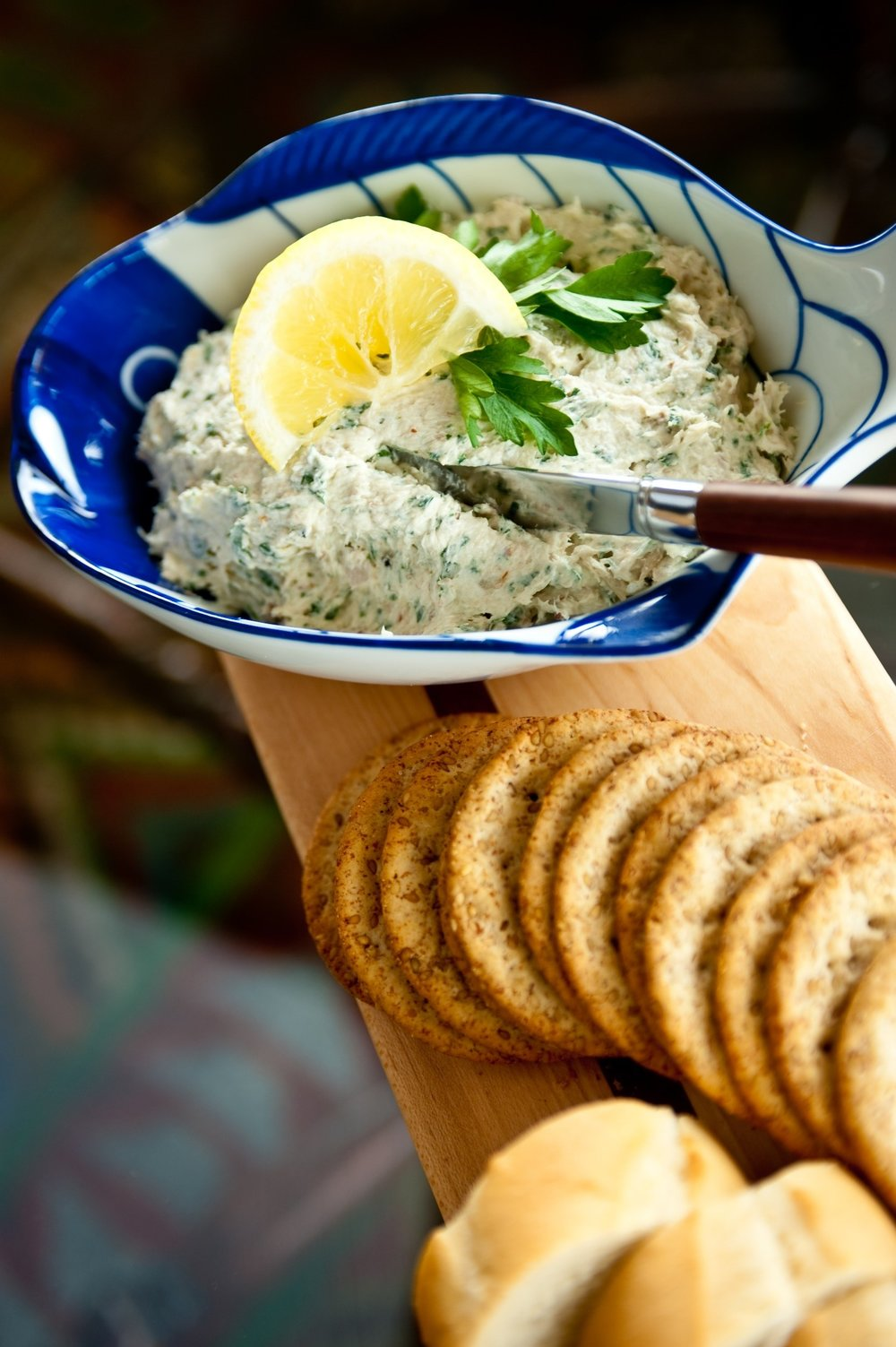 SMOKED BLUEFISH PÂTÉ. - ½ pound smoked bluefish (peppered, if available)1 package cream cheese (8 ounces), at room temperature¾ cup chopped parsley¼ cup chopped red onions1 – 2 tablespoons fresh lemon juiceSalt and freshly ground pepperCarefully remove the skin, bones, and any dark flesh from the fish and flake it into pieces. In a medium bowl beat the cream cheese to soften. Add the bluefish, parsley, onions, and lemon juice and beat together. Season with salt and pepper to taste. Spoon into a serving dish and refrigerate until ready to serve.Serve with crackers or thinly sliced and toasted baguettes.