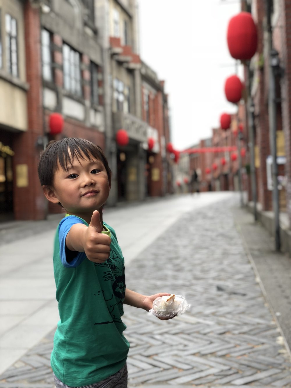 "Jude gives ""rice ball,"" a Taiwanese street food—and his new go-to snack!—a thumbs up on street at the National Center for Traditional Arts in Yilan, Taiwan."