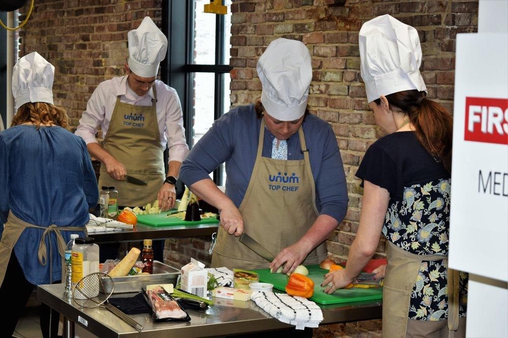 Corporate team building cooking challenge in professional kitchen