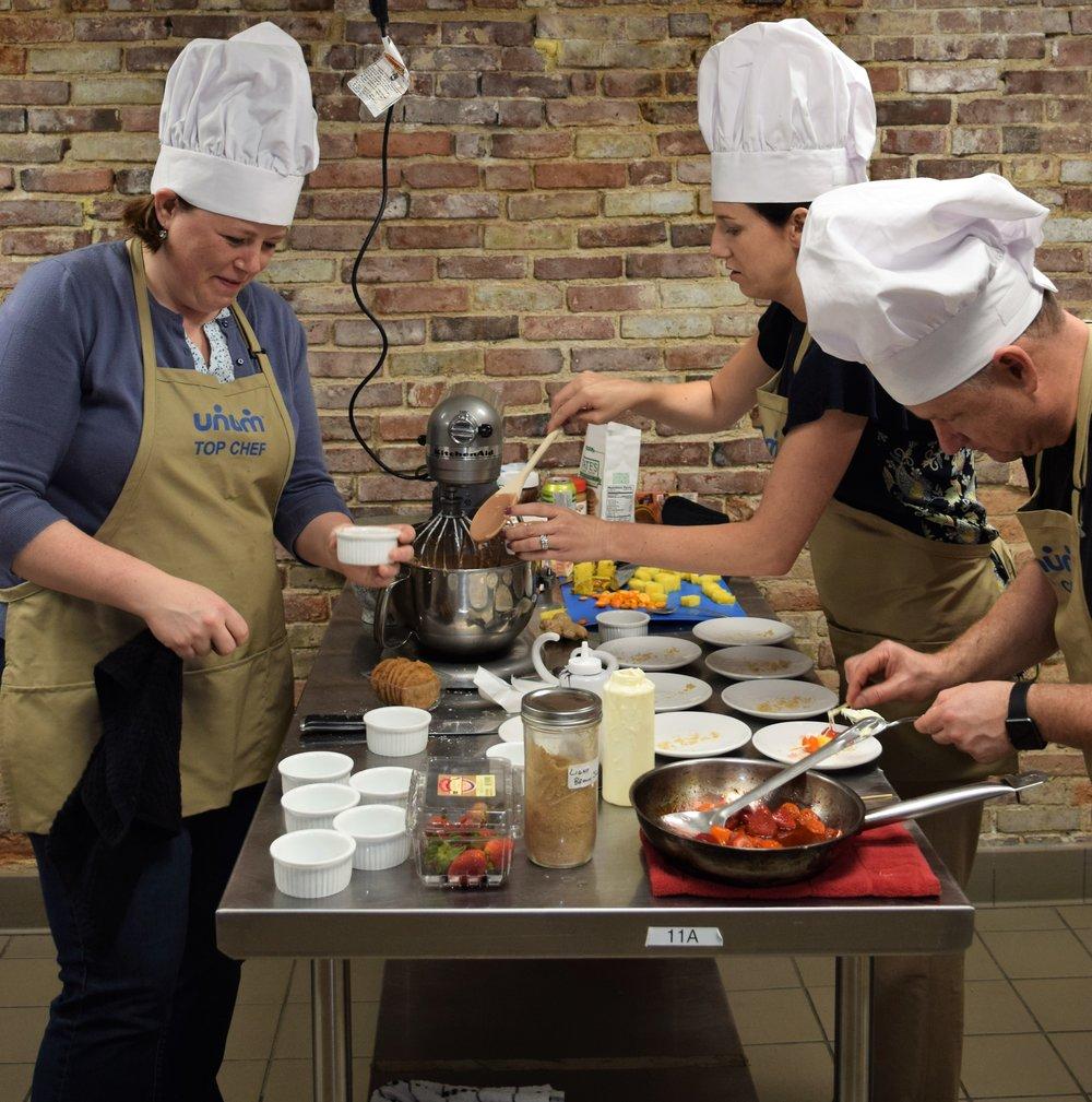 Corporate friends prepare strawberry dessert in cookoff