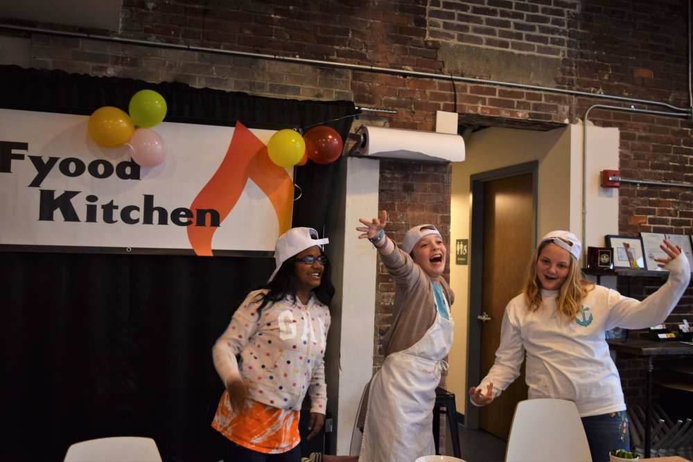 Fun teen girls presenting dish at cooking birthday party