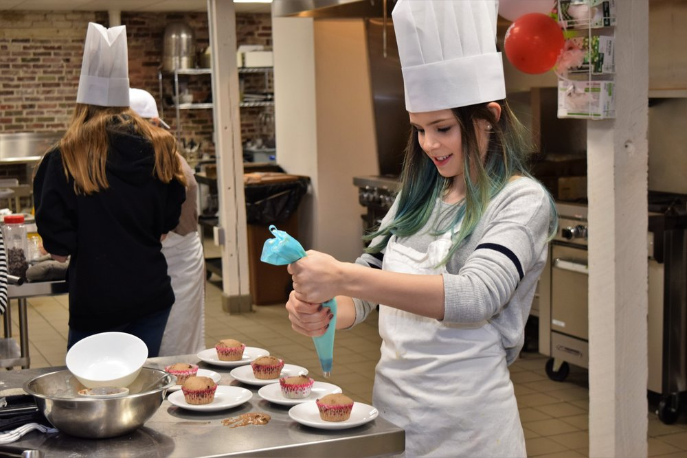 Teen birthday girl frosting cupcakes in professional kitchen
