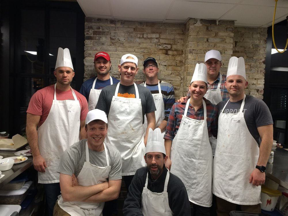 Bachelor party cooking competition group in professional kitchen
