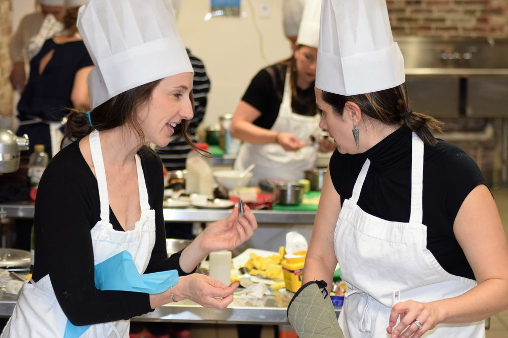 High energy action in professional kitchen with two women and pastry bag