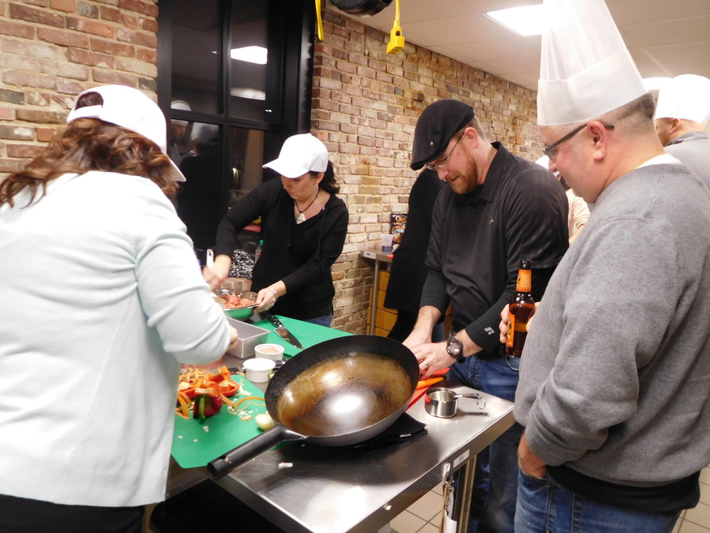 Team of amateur cooks competing with wok