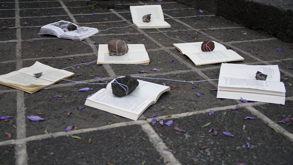 Acción Fértil 2018. Installation for performance, time-based work. Seven books, seven volcanic rocks, string.