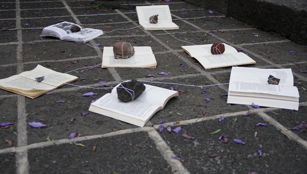 Acción Fértil 2018. Installation for performance, time-based work. Seven books, seven volcanic rocks, string.
