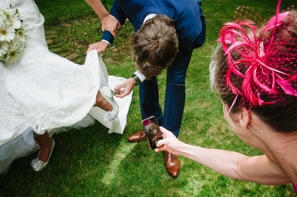 Langdale Vineyard Wedding, Jacob looks at Jodie's shoes