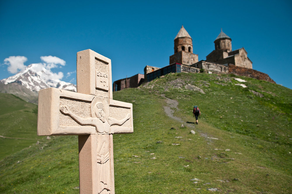 Cross and church above Kazbegi village, Georgia