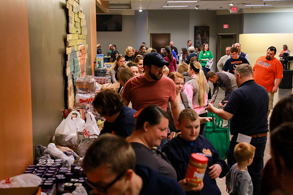 Volunteers pack bags of canned food in preparation to be delivered during the Thanksgiving Outreach