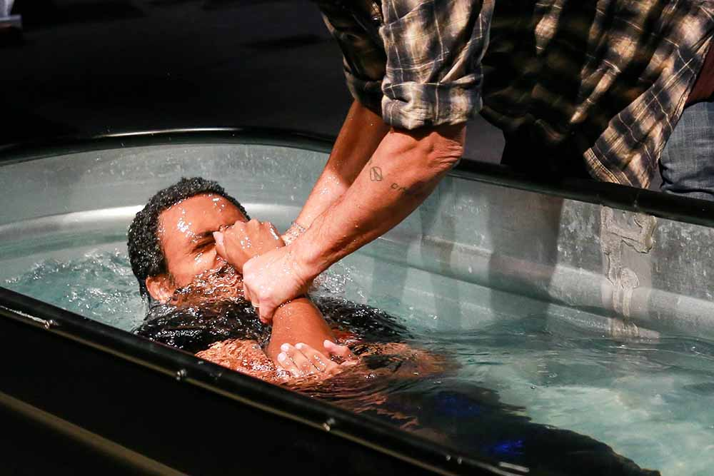 Man is lifted out of the waters of baptism during a Pulse service