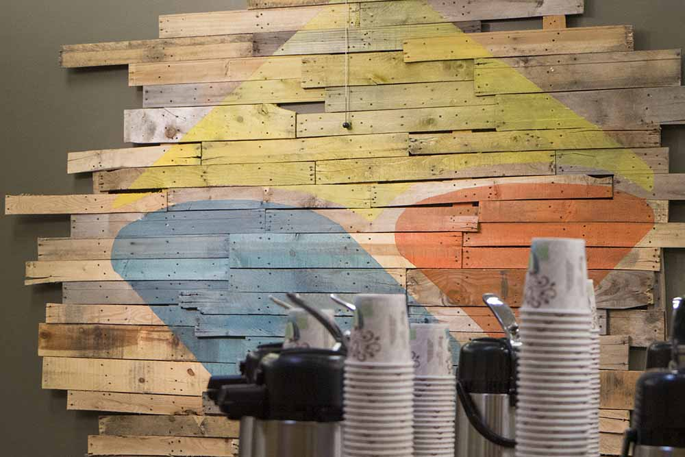 Vineyard Richmond logo superimposed on a wall of pallet wood