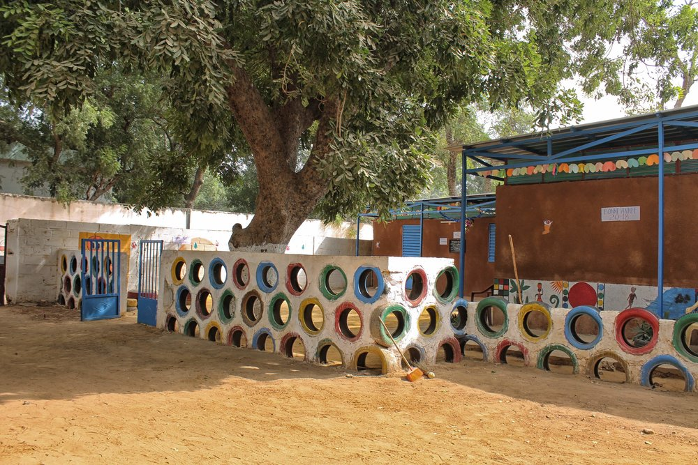 Keur Racine - Location: Quartier Dixieme, ThieSCountry: SenEgalRequirement: 2 ClassroomsType: KindergartenConstruction: May-July 2017Materials: Clay, Tyres