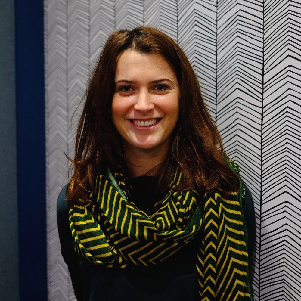 Amy Williams  stands smiling at the camera. She has medium length reddish brown hair and is wearing a dark green shirt with a patterned green and yellow scarf around her neck.