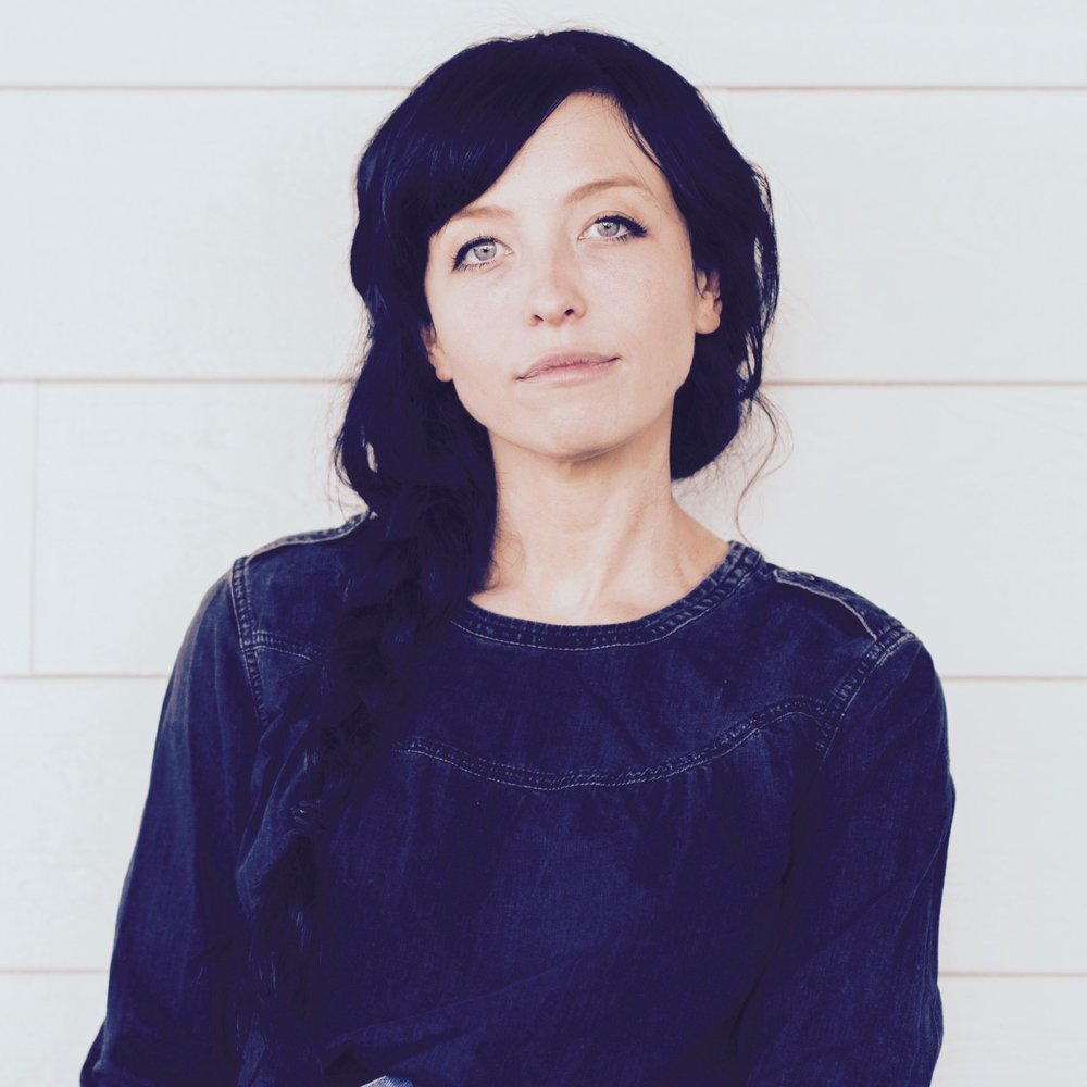 Belle Sweeney stands in front of a white wall looking at the camera. She has long black hair and is wearing a dark blue denim blouse.