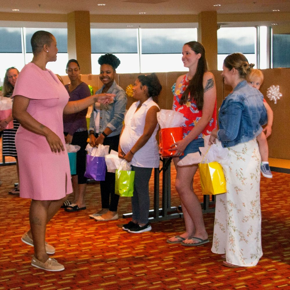 Major Jas Booth is standing, talking to a group of women. She has very short black hair and is wearing a pink knee length dress and tan loafers.