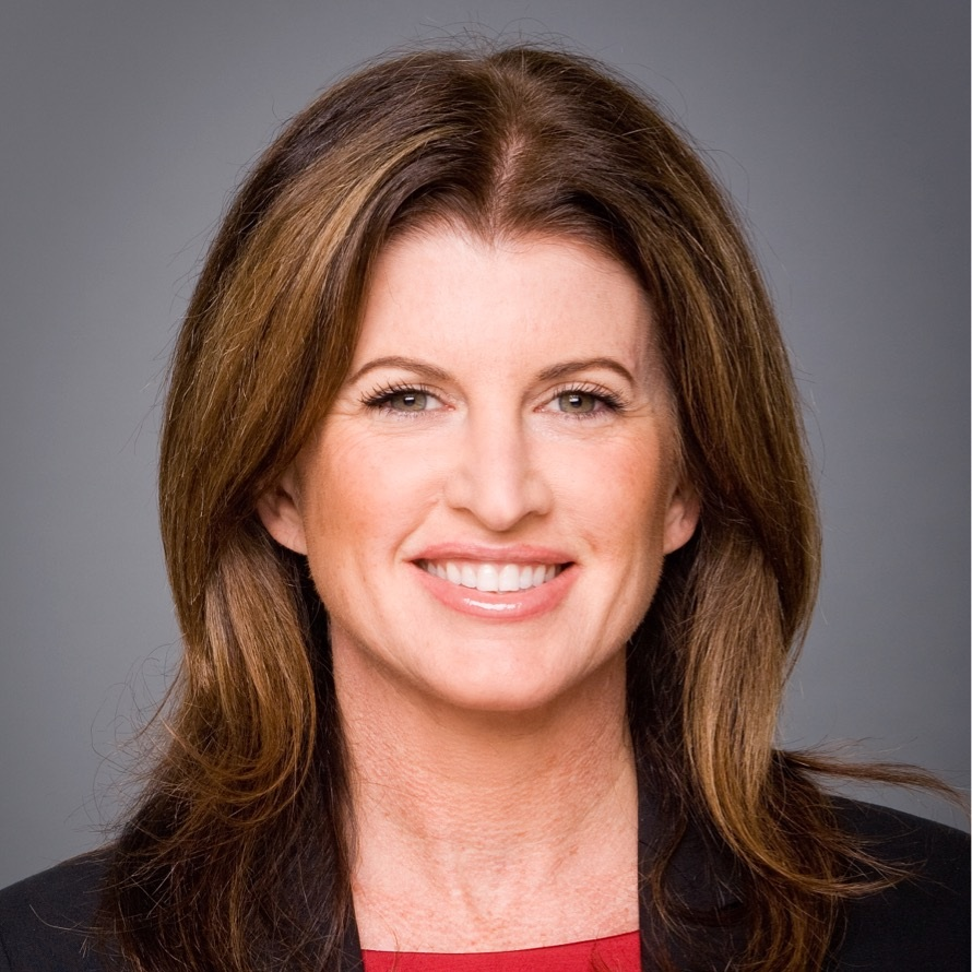 The Honorable Rona Ambrose is smiling at the camera. She has medium length brown hair and is wearing a black blazer over a red blouse.