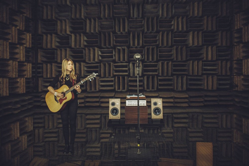 Beatie Wolfe stands in a music studio holding a guitar. She has long blonde hair and is wearing all black.