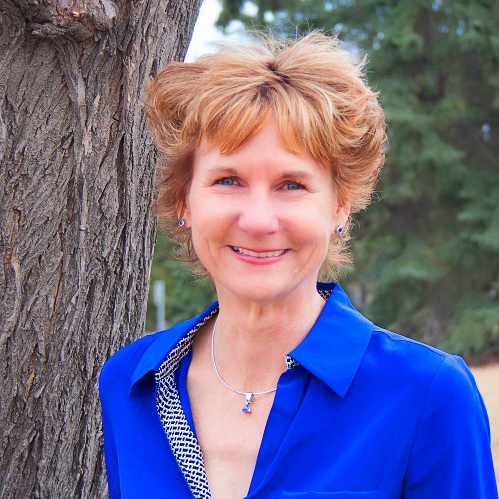 Suzanne Tough stands outside in front of a tree, smiling at the camera. She has short strawberry blonde hair and is wearing a bright blue blouse.