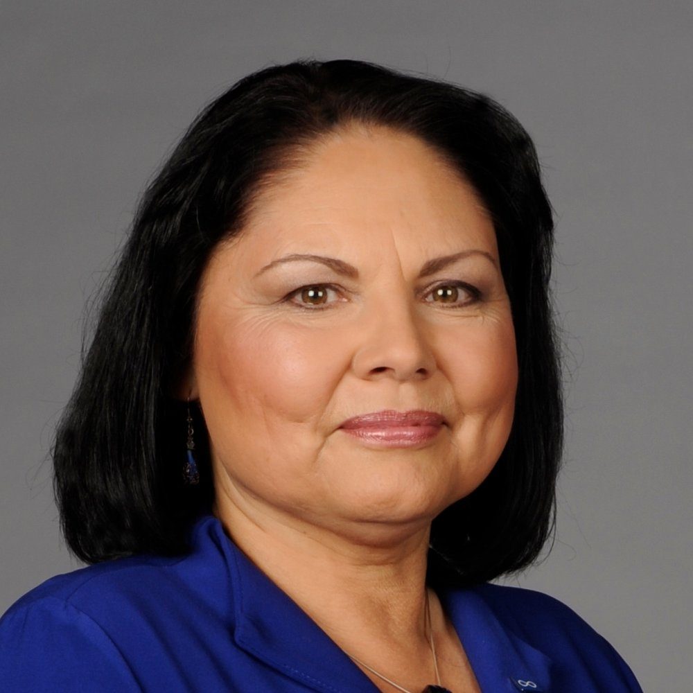 Dr. Marie Delorme sits smiling at the camera. She has shoulder length black hair and is wearing a royal blue blouse.