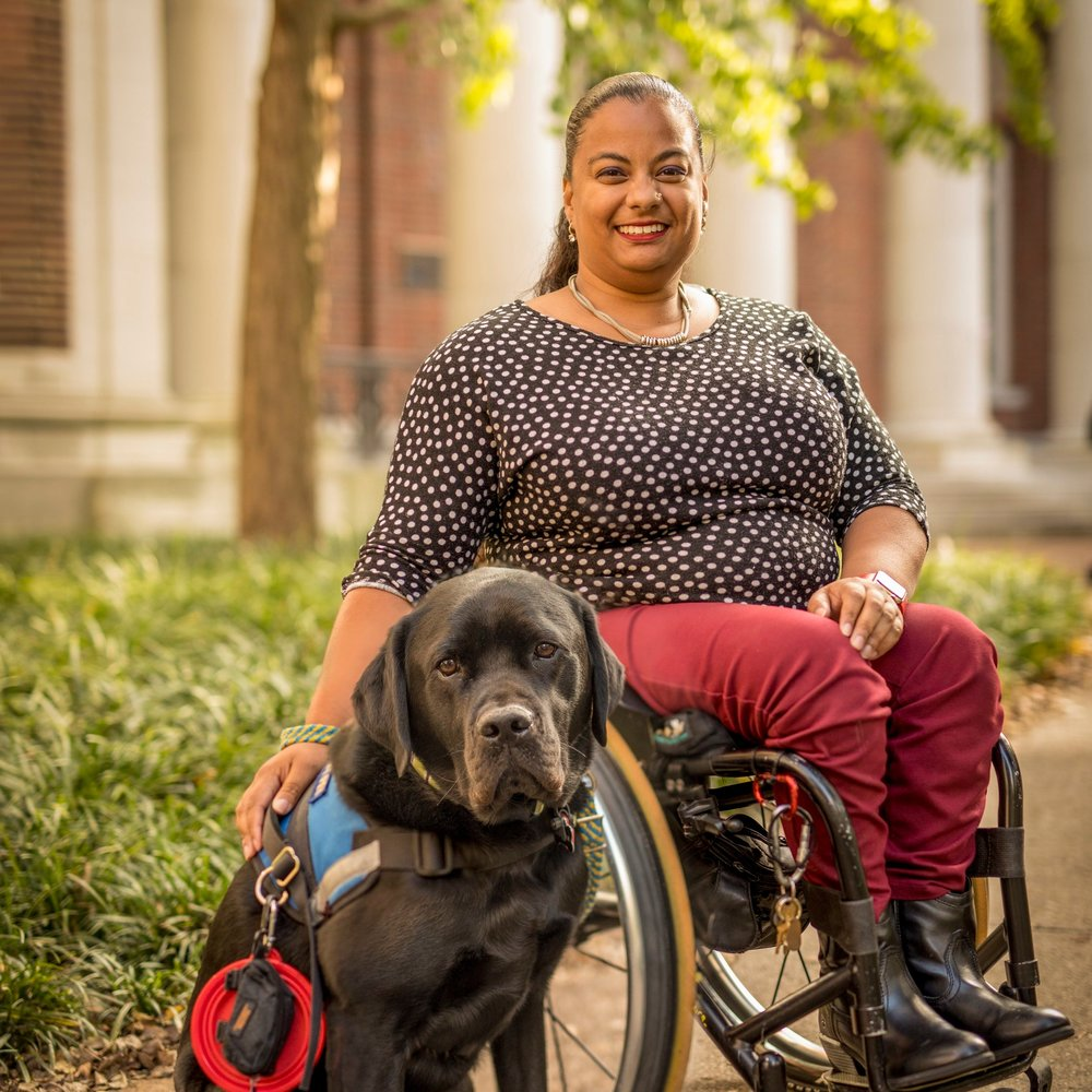 Anjali J. Forber-Pratt sits in a wheelchair, smiling at the camera, with a large black service dog by her side. Her hair is pulled back and she is wearing a black polka dot top with red pants and black boots.