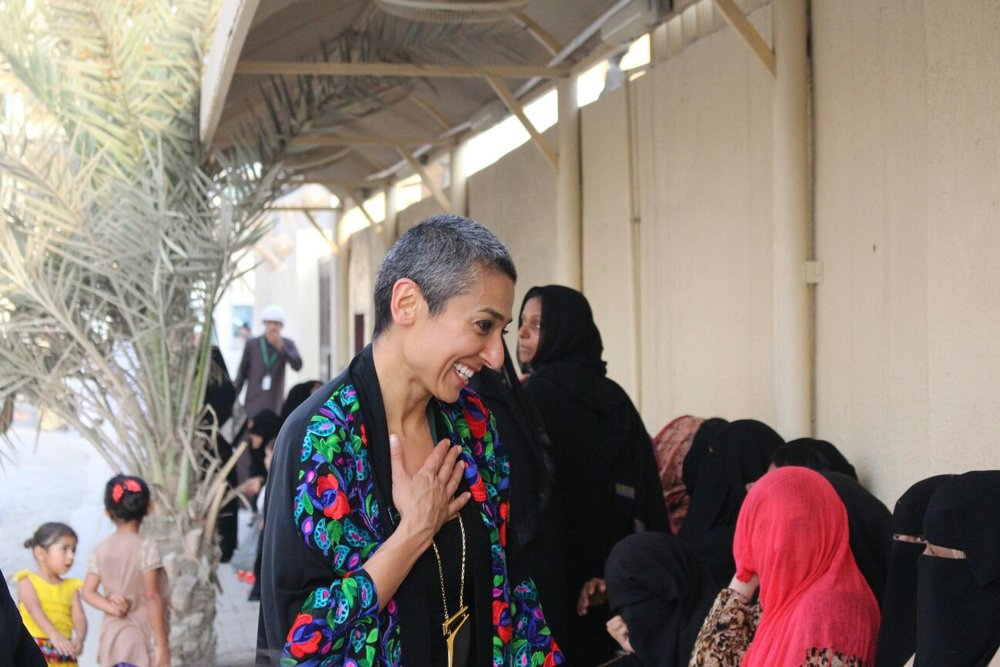 Zainab Salbi stands outside, smiling at a group of women. She has very short salt and pepper hair and is wearing a long black top with a red, blue and green pattern.