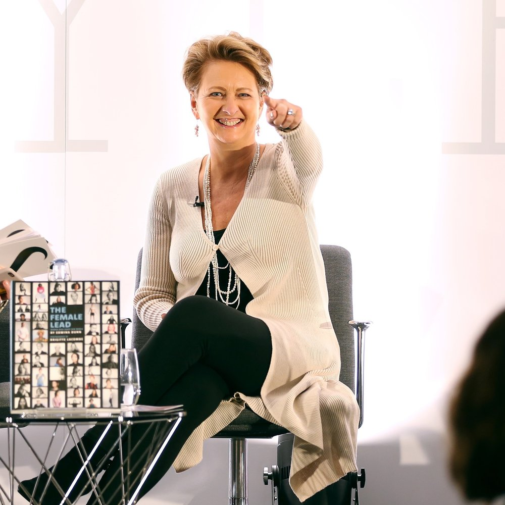 Edwina Dunn sits smiling and pointing into the camera. She has short blonde hair and is wearing a long cream cardigan and black pants.