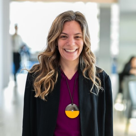 Alex Amouyel stands smiling at the camera. She has medium length blonde hair and is wearing a black blazer over a purple shirt.