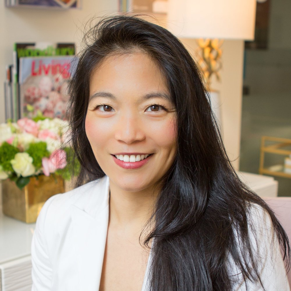 Georgene Huang sits smiling at the camera. She has long black hair and is wearing a white blazer.