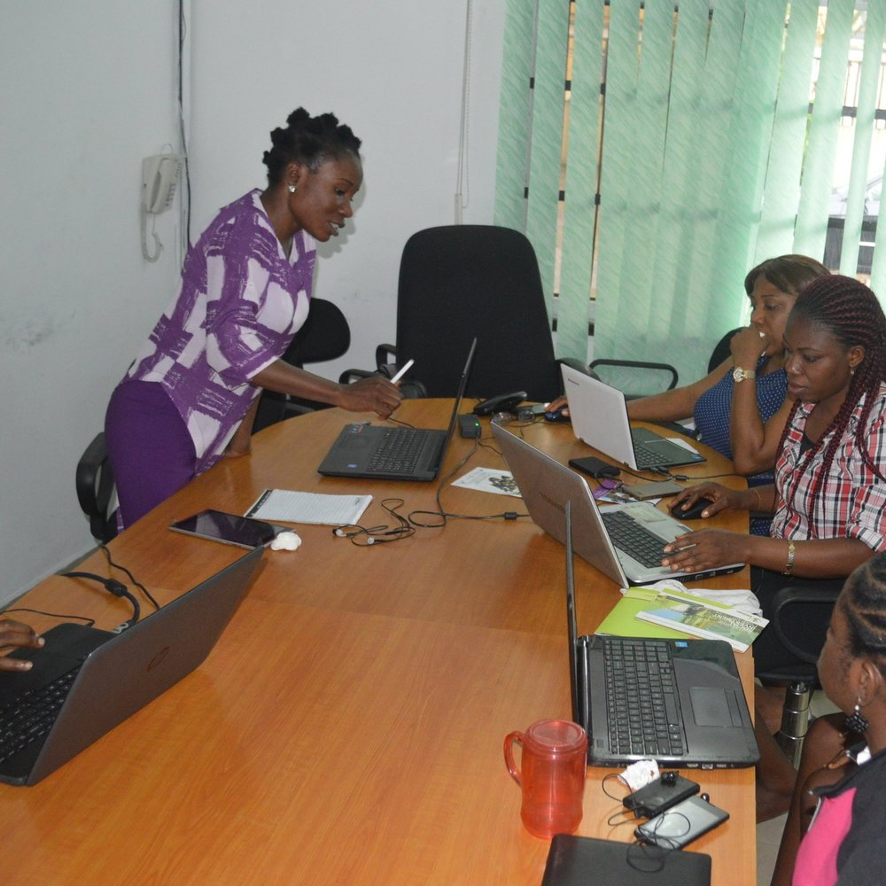 Jennifer Amadi stands working at a laptop in front of several other who women are also working on laptops around a table. She has short black hair and is wearing a purple and white shirt with purple pants.