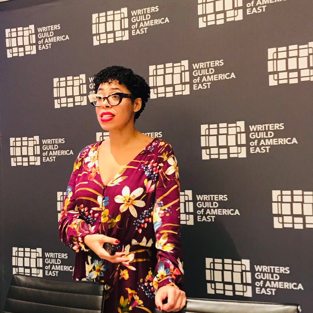 """Dr. Knatokie Ford is standing in front of a backdrop that reads """"Writers Guild of America East."""" She has short black hair and is wearing glasses and a wine colored, flower print dress."""