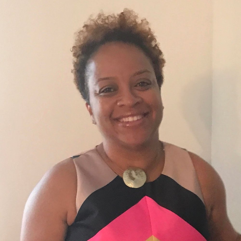 Dr. Zodelia Williams is smiling at the camera. She has very short, dark brown hair and is wearing a black and pink sleeveless blouse.